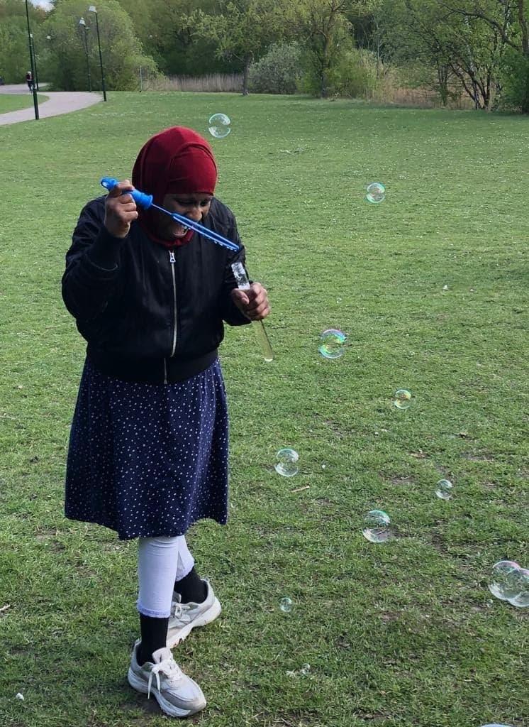 Flicka i hijab blåser såpbubblor och skrattar.